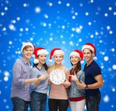 Gruppe lächelnde Studenten mit der Uhr, die 12 zeigt Lizenzfreies Stockbild