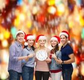 Gruppe lächelnde Studenten mit der Uhr, die 12 zeigt Stockfotografie