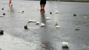 Gruppe Läufer auf Marathon nahe Punkt der Erfrischung Stapel von benutzten Wegwerfpappschalen für Wasser auf Asphalt stock video