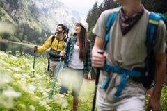 Gruppe l?chelnde Freunde, die drau?en mit Rucks?cken wandern Reise, Tourismus, Wanderung und Leutekonzept stockfotografie