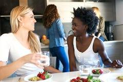 Gruppe lachende Freunde beim gesundes Lebensmittel zu Hause essen stockbild