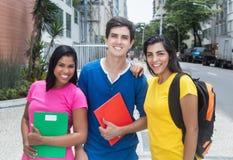 Gruppe lachende lateinamerikanische und kaukasische Studenten Lizenzfreie Stockbilder