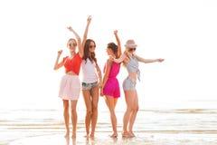 Gruppe lächelnde Frauen, die auf Strand tanzen Lizenzfreies Stockbild
