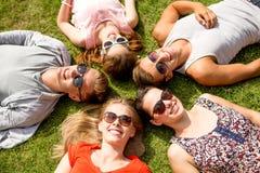 Gruppe lächelnde Freunde, die draußen auf Gras liegen Stockfotografie