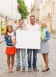 Gruppe lächelnde Freunde mit leerem weißem Brett Stockbild