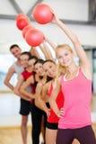Gruppe lächelnde Leute, die mit Ball ausarbeiten Lizenzfreie Stockfotos