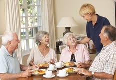 Gruppe ältere Paare Mahlzeit im Pflegeheim mit Haushaltshilfe zusammen genießend Stockfotografie
