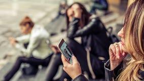 Gruppe Mädchen, die auf der Stadttreppe mit Smartphone sitzen Stockbild