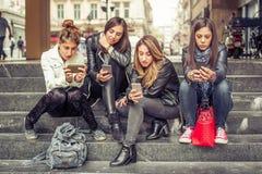 Gruppe Mädchen, die auf der Stadttreppe mit Smartphone sitzen Lizenzfreie Stockbilder