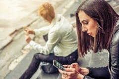 Gruppe Mädchen, die auf der Stadttreppe mit Smartphone sitzen Stockbilder