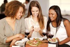 Gruppe Mädchen, die einen Smartphone betrachten Stockbild