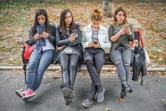Gruppe Mädchen, die Mobiltelefone auf Parkbank verwenden Stockbild