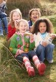 Gruppe Mädchen, die zusammen Kuchen auf dem Gebiet essen stockbild