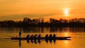Gruppe Männer, die über dem Fluss bei Sonnenuntergang rudern stockfotografie