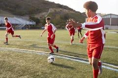 Gruppe männliche hohe Schüler, die im Fußball-Team spielen lizenzfreie stockfotografie