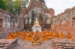 Gruppe Mönche, die in ruiniertem Gebäude von Wat Choeng Tha Temple sitzen Lizenzfreie Stockfotos