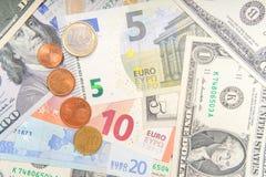 Gruppe Münzen auf Hintergrund von verschiedenen Euro- und Dollarbanknoten stockbild