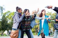 Gruppe Mädchen, die mit Gewehr vom Räuber gedroht werden Stockbilder