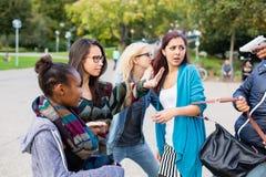 Gruppe Mädchen, die mit Gewehr vom Räuber gedroht werden Stockfotografie
