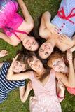 Gruppe Mädchenjugendliche im Park auf Gras Stockfotografie