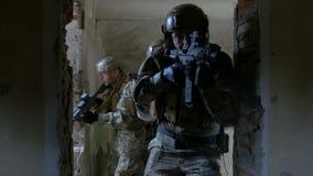 Gruppe Militärsoldaten bei der Ausbildung bewaffnet an der taktischen Übung in einem verlassenen Gebäude stock footage