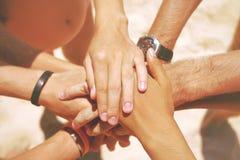 Gruppe Mischrasse-Hippie-Freunde auf dem Strand mit ihren Händen gestapelt Arme von jungen Leuten mit auf Stapel lebensstil Stockbild