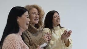 Gruppe Mischrassefrauen auf weißem lokalisiertem Hintergrund Die Mädchen betrachten das Verpacken und lachen Slowmotion stock video