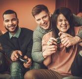 Gruppe multi ethnische Freunde, die den Spaß spielt auf Spielkonsole im Hauptinnenraum haben Lizenzfreie Stockfotos