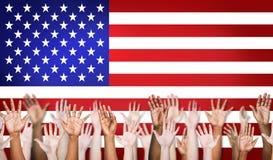 Gruppe multiethnische Arme ausgestreckt mit nordamerikanischer Flagge stockfotografie
