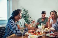 Gruppe multiethnische Freunde, die Abendessen genießen Lizenzfreie Stockfotografie
