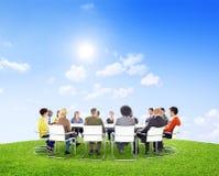 Gruppe multiethnische Leute draußen in einer Sitzung Stockbild