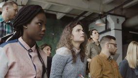 Gruppe multiethnische Leute sitzen im Dachbodenbüro und hören das Geschäftsseminar Mann und Frau konzentriert auf Seminar stock footage