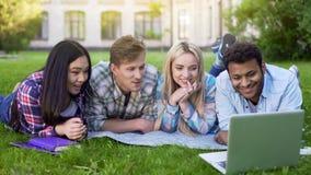 Gruppe multiethnische Studenten, die auf Gras und aufpassendem Video auf Laptop sich entspannen stockbilder