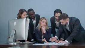 Gruppe multiethnische verschiedene junge Geschäftsleute in einer Sitzung, die um eine Tabelle mit ernsten Ausdrücken steht Lizenzfreie Stockfotografie