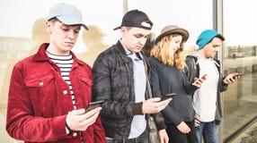 Gruppe multikulturelle Freunde, die Smartphone an der Universität verwenden lizenzfreie stockfotografie