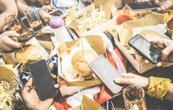 Gruppe multikulturelle Freunde, die Spaß auf Smartphone am resta haben stockbilder