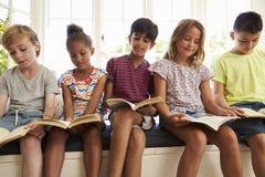 Gruppe multikulturelle Kinder, die auf Fensterplatz lesen stockbild