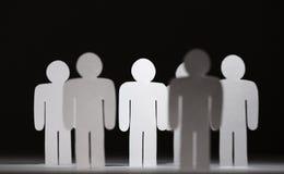 Gruppe papermen auf schwarzem Hintergrund Stockbild