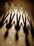 Gruppe Papierleutehändchenhalten. Stockfoto