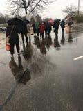 Gruppe Pendler, die nach Hause im Regen vorangehen Lizenzfreie Stockfotos