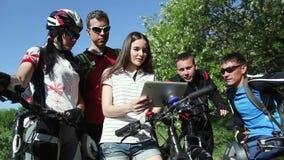 Gruppe Radfahrer, welche die Karte in der Tablette den Weg besprechend überprüfen stock video