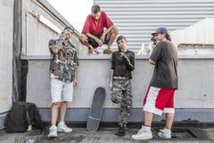 Gruppe Rapper, die gegen die Wand auf den Metalldachspitzen aufwerfen stockfotos