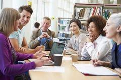 Gruppe reife Studenten, die auf Projekt in der Bibliothek zusammenarbeiten Lizenzfreies Stockfoto