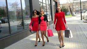 Gruppe reizende Freundinnen, die hinunter die Straße nach einem Einkaufstag gehen Junge Frauen in den schönen Kleidern mit stock video footage
