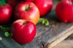 Gruppe rote Äpfel auf hölzernem natürlichem Hintergrund, neuer Naturkost und Vitaminkonzept in der rustikalen Art Stockfotografie