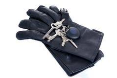 Schlüssel auf den schwarzen ledernen Handschuhen lokalisiert stockfotografie