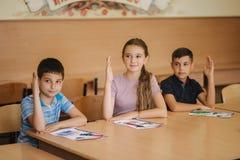 Gruppe Schulkinder mit Stiften und Notizbücher, die Test in Klassenzimmer schreiben Ausbildung, Volksschule, lernend und lizenzfreie stockfotografie