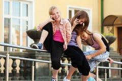 Gruppe Schulmädchen, welche um die Handys ersuchen Stockfoto