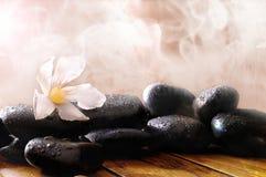 Gruppe schwarze Steine auf hölzerner Basis mit Dampfhintergrund Lizenzfreies Stockfoto