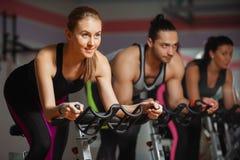 Gruppe Sitzleute, die in Fitness-Club radfahren stockfoto